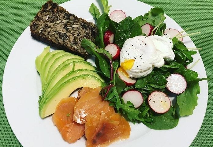 mix zelených salátů se ztraceným vejcem, uzeným lososem a avokádem