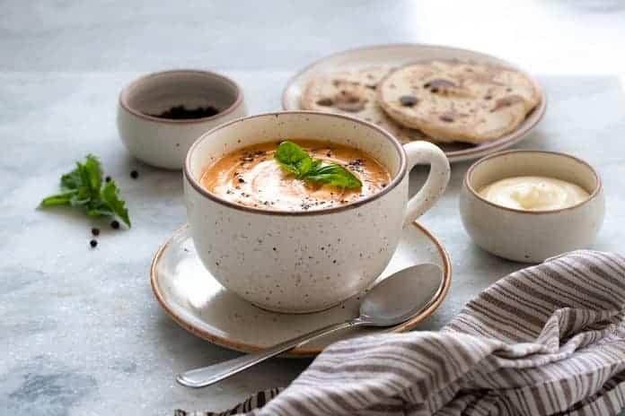 dýňová polévka zahuštěná bramborem ozdobená dýňovými semínky